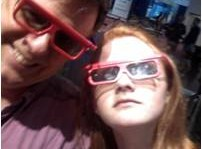 A father and daughter wearing IMAX theater glasses