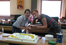 "two students laugh with cake on their face. The cake reads, ""Welcome to OCES at W&M"""