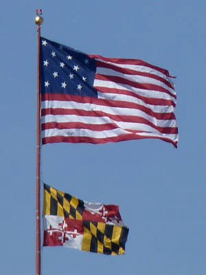 American and Maryland flags flying high over downtown Baltimore. Just why does the American flag have 15 stars and stripes? Think about Baltimore's Fort McHenry and Francis Scott Key.