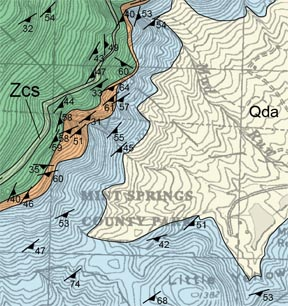 Small part of the Geologic Map of the Crozet 7.5' quadrangle (map   illustrates a 1.5 x 1.5 km area).  Different colors represent different   rock units exposed at the surface and the dark symbols are rock   structures.  The light yellow unit (Qda) is underlain by sedimentary   deposits formed from debris flows and mudslides.