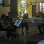 an impromptu saxophone quartet performing in a piazza for diners and passersby