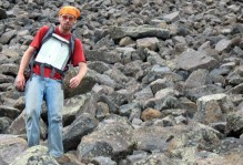 a man backpacking over rocks