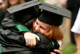 two people in cap and gowns hugging