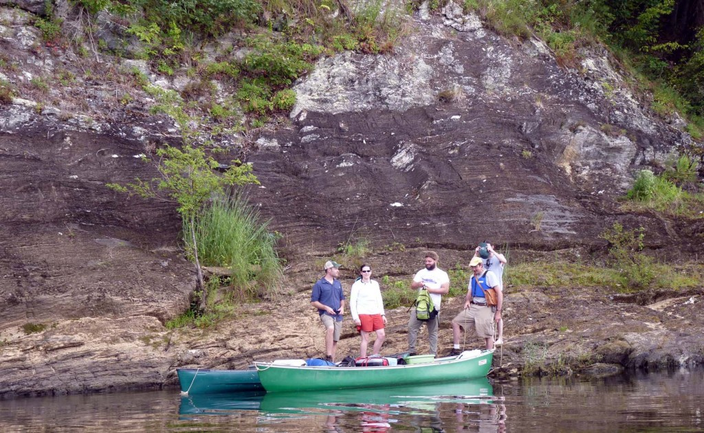 On the outcrop, the field crew poses with part of the flotilla at the James River's edge.