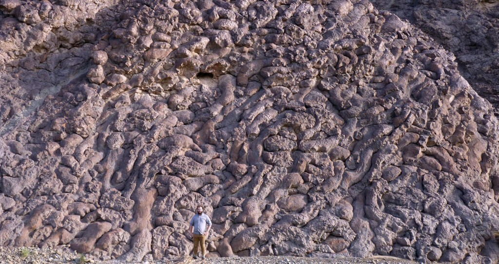 Alex Johnson, William & Mary Geology Fellow, standing tall and proud in front of the pillow lavas exposed at Wadi Jizzi, northern Oman
