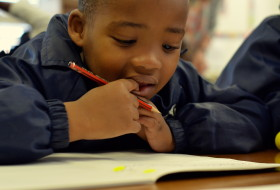 close up of a young kid with a pencil in hand