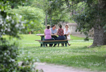 Family sitting at a picnic table on campus