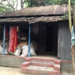 A house built with a Grameen Bank loan. The walls and roof are corrugated tin and there are multiple rooms and a porch.