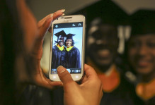 Picture of two students on a phone at Commencement in regalia