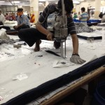 A factory worker cutting thick layers of fabric with a blade.