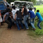 Villagers pulling our van out of the mud before it tumbles down into rice patties.