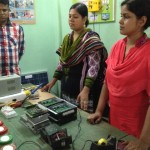 Women learning technical skills to fix village electronics.