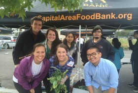 "a group poses in front of a tent that reads ""Capital Area Food Bank.org"""