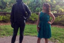 Emily Wynn standing next to a statue