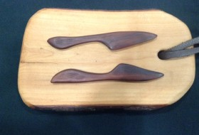 a wooden cheeseboard with wooden knives
