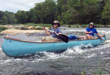 two men in a canoe on rapids