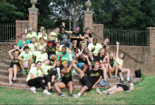 a group of Deans vs. Interviewers after kickball sitting on the steps of the sunken gardens