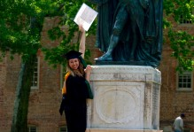 a graduating student holds up their degree next to the statue in front of the wren building