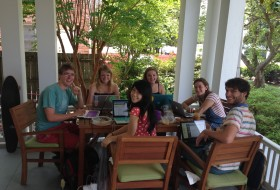 students eating around a table while working on laptops