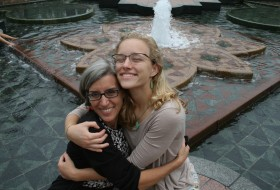 a student hugs her mom in front of a fountain