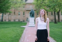 A picture of Anne Davis '16 in front of the wren building