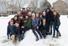 Smiling students sitting on a pile of snow