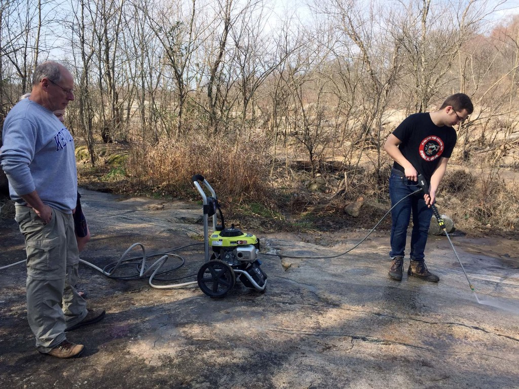 William & Mary geology major Tyler Skelton power-washing an outcrop, Professor Brent Owens works on his managerial skills.