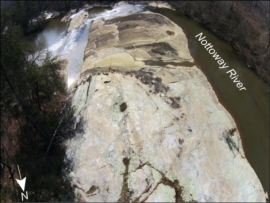 Oblique aerial view to the south of the uppermost outcrop at the Falls of the Nottoway, Virginia. At high water conditions, the Nottoway River flows over the top 1/3 of the outcrop, which is stained with a patina of iron and manganese oxides as well as a thin coating of sediment. In the upper part of the outcrop (the foreground) the granitic gneiss is rarely covered by water and the bedrock is better exposed.