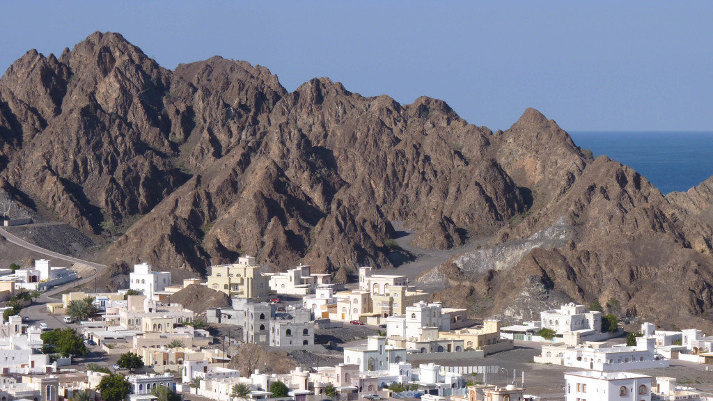 The village of Qantab, Oman with the waters of the Gulf of Oman visible in the distance. The craggy and steep hills are underlain by Cretaceous ophiolite.