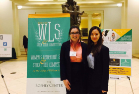 two women pose in front of the WLS sign