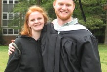 a man and woman pose together in their graduation outfits