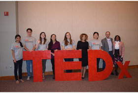 students pose behind a TEDx sign