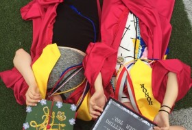 Two Graduating students lying with their decorated caps covering their faces