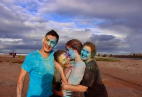 A family (3 girls, one boy) smiles and embraces with blue paint all over them