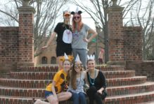 5 students wearing party hats pose on the steps in the sunken garden.