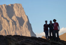 William & Mary geology students silhouetted in shadow below Jebel Misht, Oman.