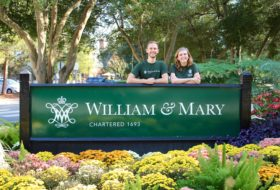 Two students pose in front of a William & Mary college sign during Homecoming 2017