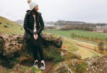 student sits atop rock and looks out into the distance at a field