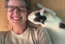 black and white kitten gives smiling girl a peck on the cheek