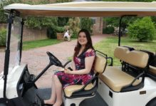 Women smiles posing for picture in the front seat of a white golf cart