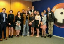 Group Poses for picture next to PBS logo at the News and Media Summer Institute at PBS.