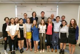 "Former FBI Director and William and Mary alum James Comey poses with the News & Media Institute. Standing in front of him at center is Kyra, who later said, ""You could fit another half of me on top and I still wouldn't be as tall as him!"""