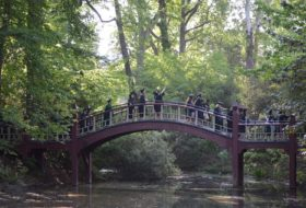Seniors dressed in cap and gown cross the Crim Dell Bridge