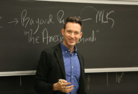a professor lecturing in front of a chalk board
