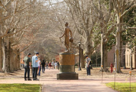 passers by stop in front of Monroe statue on old campus