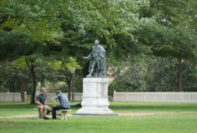 two people sit on a bench in front of Lord Botetourt statue in Wren Yard