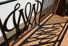 Cypher shadow from wrought iron gate on bricks
