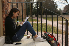 Female student on wren steps writing in notebook.
