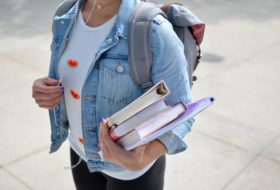 Student carrying her textbooks in her arm