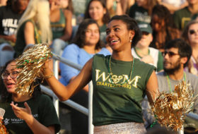 Female student with gold pompoms cheering at a Tribe football game